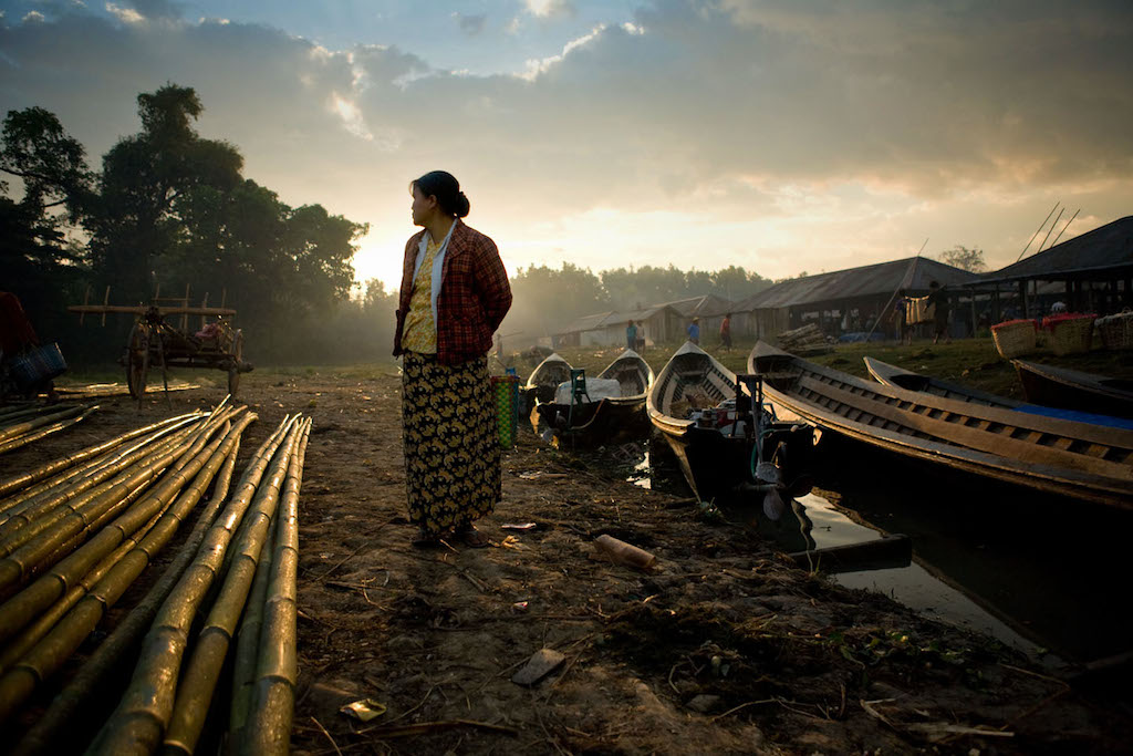 A woman stands at the boat docks at a market in Inlay Lake, Burma.  (Photo by Robb Elliot/Momenta Workshops)